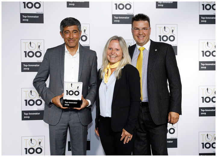 Heike Fricke and Matthias Kluczinksi of eurolaser (center and right, respectively) receive the award as TOP 100 innovator from Ranga Yogeshwar (left).